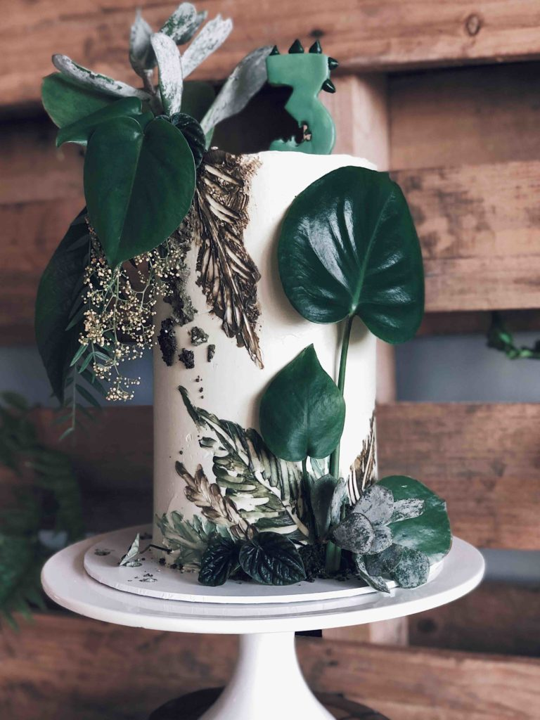 We love creating Ged's cakes every year. Krystal has that attention to detail we just love falling down the rabbit hole with.<br> <br> With a brief in mind Krystal described the elements  and styling she was incorporating on the day. Foliage back drops, gold dino centrepieces and an array of dino themed treats. We wanted to blend our design with the styling already established. So we started creating.